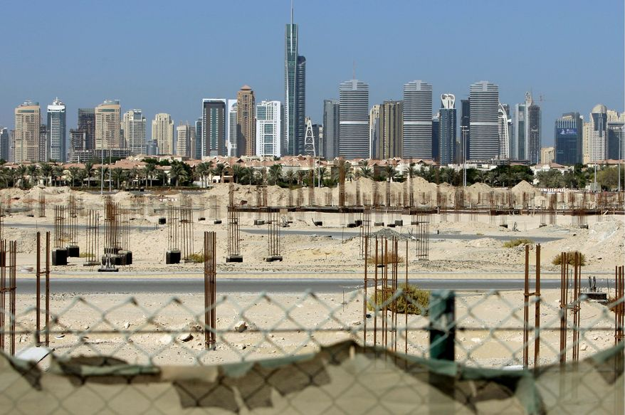 ASSOCIATED PRESS PHOTOGRAPHS Dubai Marina towers form the backdrop to a construction site that has been stalled since a financial crisis hit Dubai in 2009.