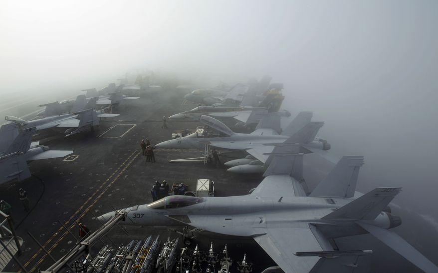 U.S. Navy F/A-18F Super Hornet fighter attack aircraft sit in heavy fog on the deck of the USS George Washington during joint military exercises with South Korean forces off that country's west coast on Tuesday, Nov. 30, 2010. (AP Photo/Wally Santana)
