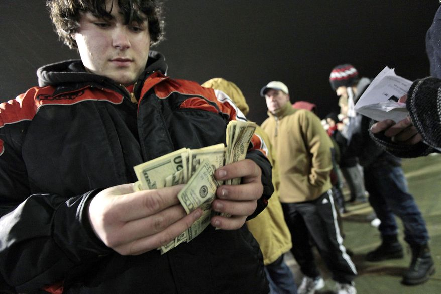 Kyle Pinard makes a last-minute accounting of how much money he has to spend as he waits in line with other shoppers at a Best Buy in Dartmouth, Mass., on Friday, Nov. 26, 2010. Americans' confidence rose to a five-month high in November amid more hopeful signs for the economy. (AP Photo/The Standard Times of New Bedford, Peter Pereira)