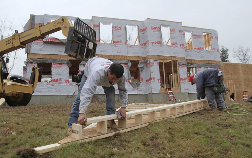 In this Nov. 16, 2010, photo, builders nail together a roof panel for a second-story home under construction in Derry, N.H. Home prices are falling faster in the nation's largest cities, and a record number of foreclosures are expected to push prices down further through next year. (AP Photo/Charles Krupa)