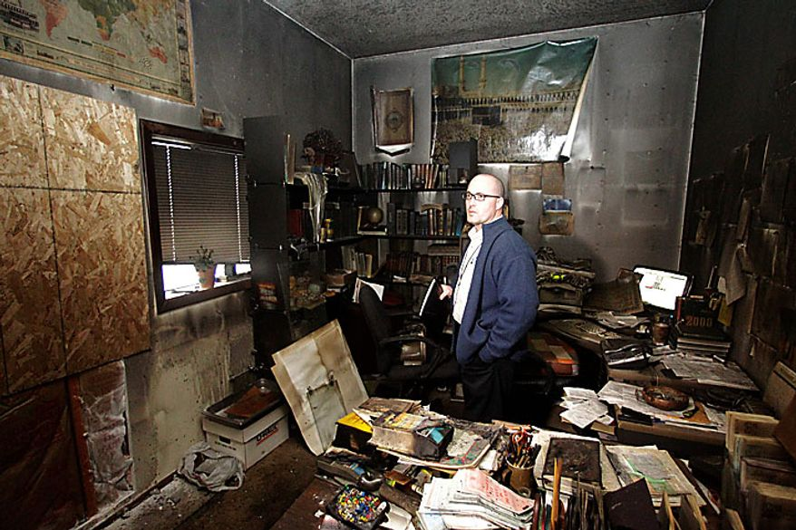 Cpt. Jonathan Sassman, of the Corvallis Police Department looks over fire damage at the Salman Al-Farisi Islamic Center in Corvallis, Ore., Sunday, Nov. 28, 2010, where an alleged arsonist set a fire in the early morning hours. Anger on Sunday over a Somali-born teen's failed plan to blow up a van full of explosives during Portland's Christmas tree lighting ceremony apparently erupted in arson on Sunday when a fire damaged the Islamic center once frequented by the suspect. (AP Photo/Rick Bowmer)