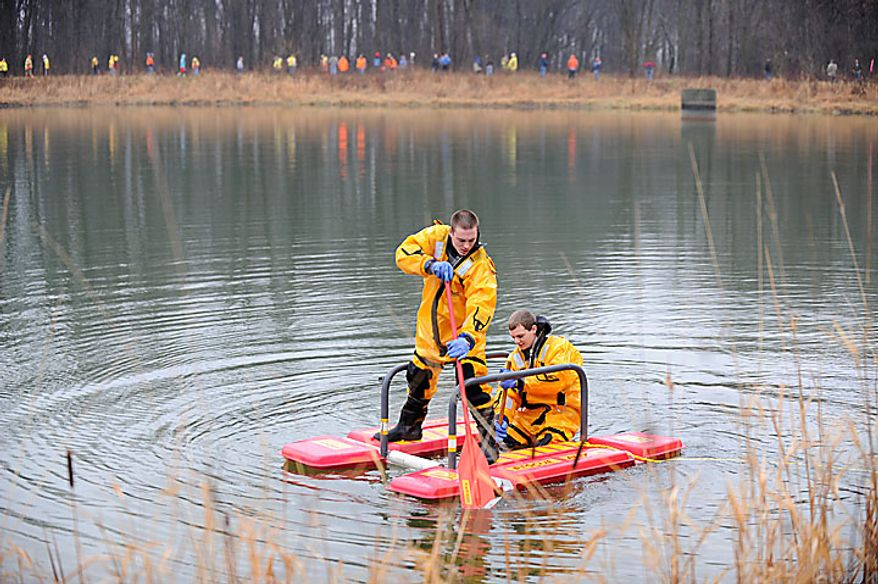 "Joel Hess, left, and Brandon Stewart, both from an ice rescue team for Cambridge Township Fire Dept.  search for 9-year-old Andrew, 7-year-old Alexander and 5-year-old Tanner Skelton in a small pond in Morenci, Mich. on Tuesday, Nov. 30, 2010. Authorities ""do not anticipate a positive outcome"" in the search for three Michigan brothers who have been missing since their father's attempted suicide, a police chief said Tuesday. (AP Photo/The Detroit News, David Coates)"