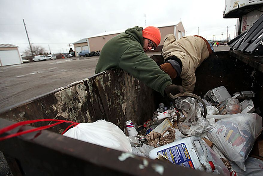 """Volunteers David Patterson, of Archbold, Ohio, left, and Matthew Poorman, of Swanton, Ohio, search a dumpster behind Hutches Towing as the search for 9-year-old Andrew, 7-year-old Alexander and 5-year-old Tanner Skelton continues in Holiday City, Ohio on Tuesday, Nov. 30, 2010. Authorities """"do not anticipate a positive outcome"""" in the search for three Michigan brothers who have been missing since their father's attempted suicide, a police chief said Tuesday. (AP Photo/Detroit Free Press, Andre J. Jackson)"""