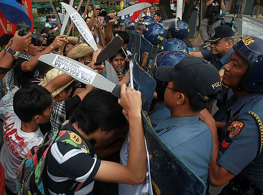 Protesters are blocked by riot police as they surge towards the U.S. Embassy in Manila, Philippines, Tuesday Nov. 30, 2010, to rally against the presence of American troops for the joint US-Philippines military exercise known as the Visiting Forces Agreement or VFA, which they claim has provided legal cover for the occupation of foreign troops in the Philippines. (AP Photo/Bullit Marquez)