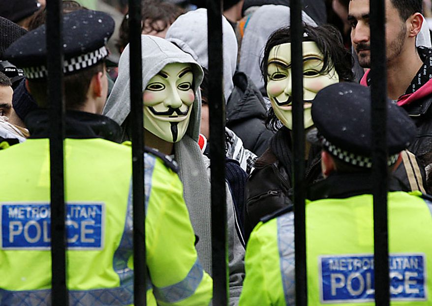 British police officers contain a group of students protesters outside Buckingham Palace in London, Tuesday Nov. 30, 2010, during a protest against tuition fees. British students held a third day of protests over plans to triple university tuition fees, with police urging them to avoid the violence that marked earlier demonstrations. School and university students braved snow in London for a rally in Trafalgar Square against the decision to increase university fees to 9,000 pounds ($14,000) a year as part of government deficit-cutting measures.(AP Photo/Sang Tan)
