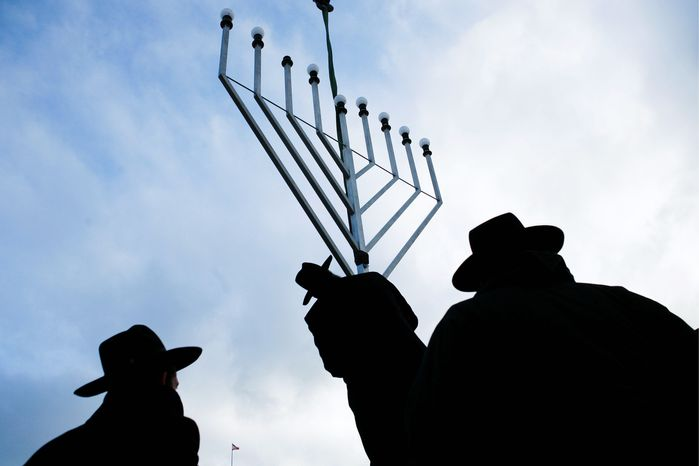 ASSOCIATED PRESS Rabbi Yehuda Teichtal (center) installs a giant Hanukkah menorah with other rabbis at the launch of the eight-day Jewish festival of lights at the Pariser Platz near the Brandenburg Gate in central Berlin on Wednesday.