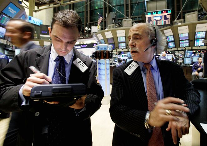 ASSOCIATED PRESS Traders Gregory Grassi (left) and Peter Tuchman confer on the floor of the New York Stock Exchange on Wednesday. The Dow Jones industrial average rose nearly 250 points, its biggest gain since Sept. 1.