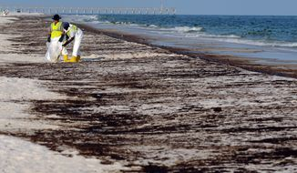 ** FILE ** Crews clean up oil that washed ashore from the Deepwater Horizon spill on Pensacola Beach in Pensacola, Fla., in June 2010. (AP Photo/Michael Spooneybarger, File)