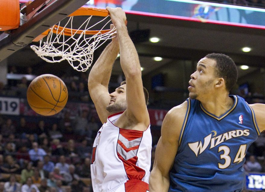 Toronto Raptors' Linas Kleiza, left, dunks the ball over Washington Wizards' JaVale McGee during first-half NBA basketball game action in Toronto, Wednesday, Dec. 1, 2010. (AP Photo/The Canadian Press, Darren Calabrese)
