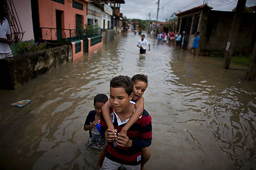 A boy carries a girl on his back through a flooded street in Higuerote, Venezuela, Tuesday Nov. 30, 2010. Flooding and landslides unleashed by torrential rains have killed at least 30 people in Venezuela and forced thousands from their homes.  (AP Photo/Ariana Cubillos)