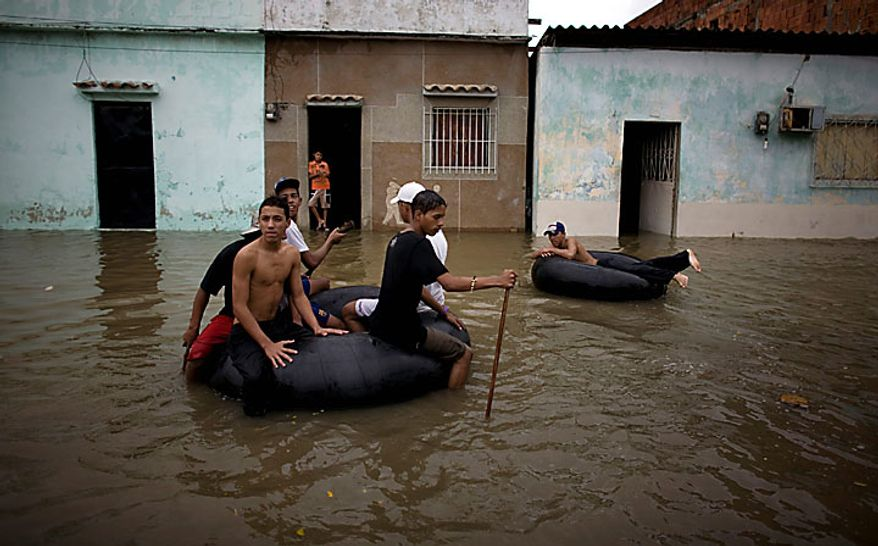 People float on inner tubes through a flooded street in Higuerote, Venezuela, Tuesday Nov. 30, 2010. Flooding and landslides unleashed by torrential rains have killed at least 30 people in Venezuela and forced thousands from their homes.  (AP Photo/Ariana Cubillos)