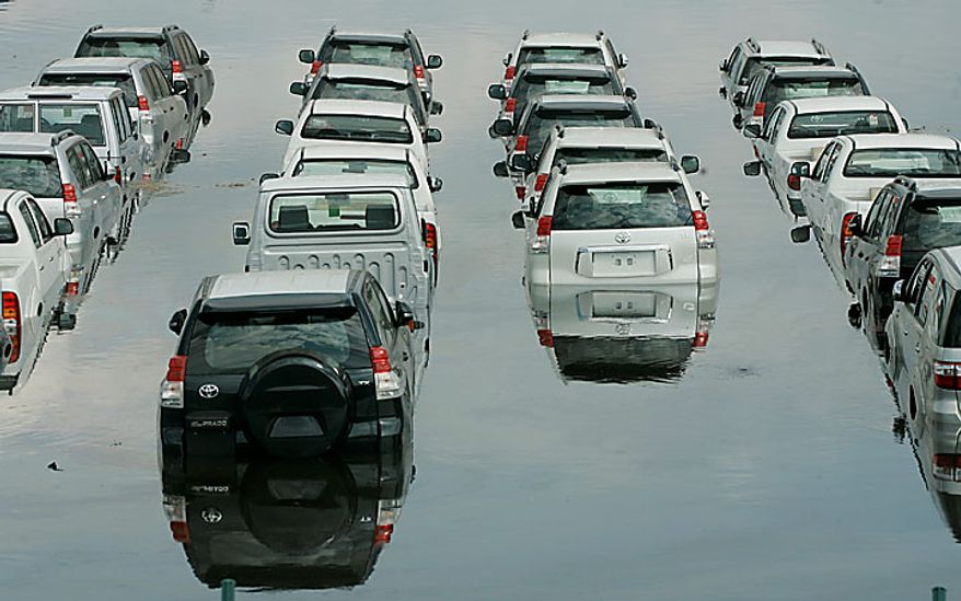 """Cars are partially covered by water at the flooded parking lot of a car importer in Palmira, southern Colombia, Tuesday, Nov. 30, 2010.  According to meteorologists the """"La Nina"""" climatic phenomenon is causing an exceptionally wet rainy season that has caused floods and landslides, killing over 130 people throughout Colombia. (AP Photo/Christian Escobar Mora)"""