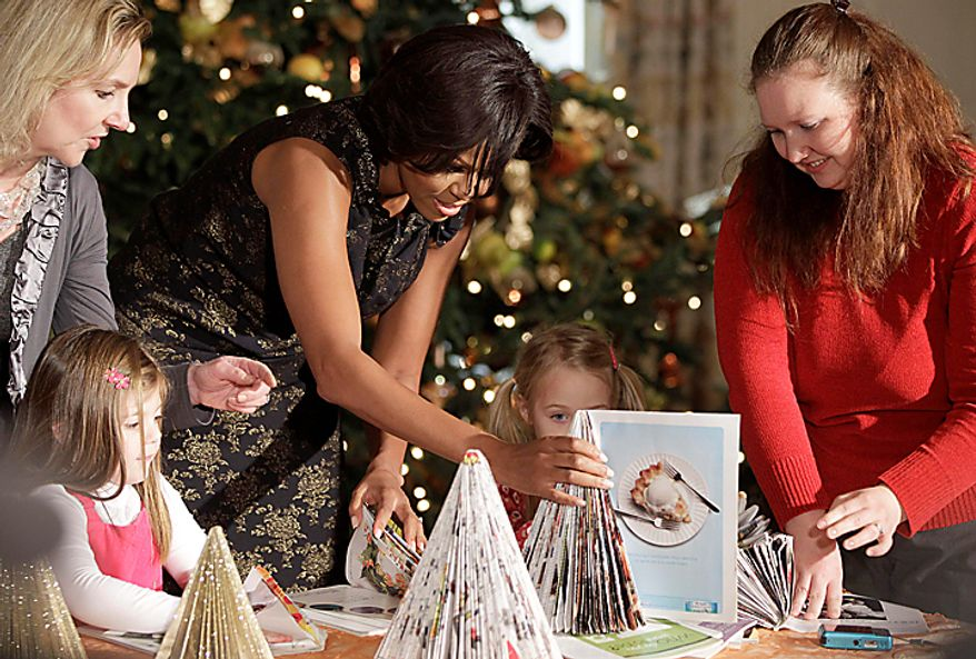 First lady Michelle Obama makes Christmas arts and crafts with children from military families, Wednesday, Dec. 1, 2010, in the State Dining Room of the White House in Washington. (AP Photo/Charles Dharapak)