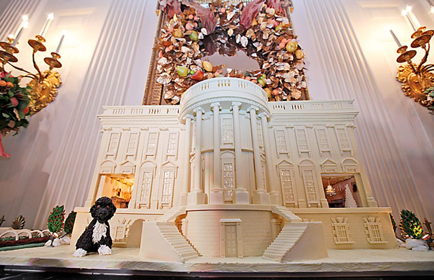 """The Obama family dog, Bo, and a marzipan replica of the White House Kitchen Garden is seen at left, as the 2010 White House Chocolate Gingerbread House is displayed in the State Dining Room of the White House in Washington, Wednesday, Dec. 1, 2010. The theme for the White House Christmas 2010 is """"Simple Gifts"""". (AP Photo/Charles Dharapak)"""
