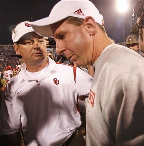FILE - This Nov. 1, 2008, file photo shows Oklahoma head coach Bob Stoops, left, greeting Nebraska head coach Bo Pelini, right, following their NCAA college football game in Norman, Okla. Oklahoma won the game 62-28. Stoops and Pelini were childhood friends and coaching colleagues before they were presiding over opposite sides of one of college football's storied rivalries. But after Stoops directs No. 10 Oklahoma against Pelini and No. 13 Nebraska in one last meeting in the Big 12 championship on Saturday, they'll head in opposite directions again as the Cornhuskers head to the Big Ten.(AP Photo/Sue Ogrocki, File)