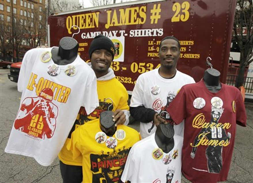 "Derrick Tatum, left, and Ralph Reynolds hold up shirts and buttons they created and are selling under the label ""Queen James 23"" in ""honor"" of NBA star LeBron James, outside Quick Loans Arena, home of the Cleveland Cavaliers, in Cleveland on Tuesday, Nov. 30, 2010.  James and his team the Miami Heat will play his old team the Cleveland Cavaliers for the first time on Thursday since leaving to play for the Heat.  Tatum and Reynolds have a chemical business in Atlanta, but decided to create the line, paint one of their trucks, and make the trek to Cleveland in anticipation of the teams' first meeting of the season since James' controversial departure. (AP Photo/Amy Sancetta)"