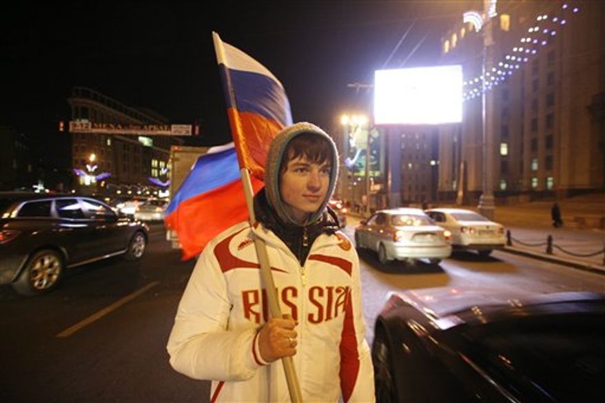 A young man holding a Russian flag hands out free national flags to motorists in downtown Moscow, to celebrate FIFA's selection of Russia as host to the 2018 World Cup, Thursday, Dec. 2, 2010. Russia was announced as host of the 2018 tournament. (AP Photo/Pavel Golovkin)