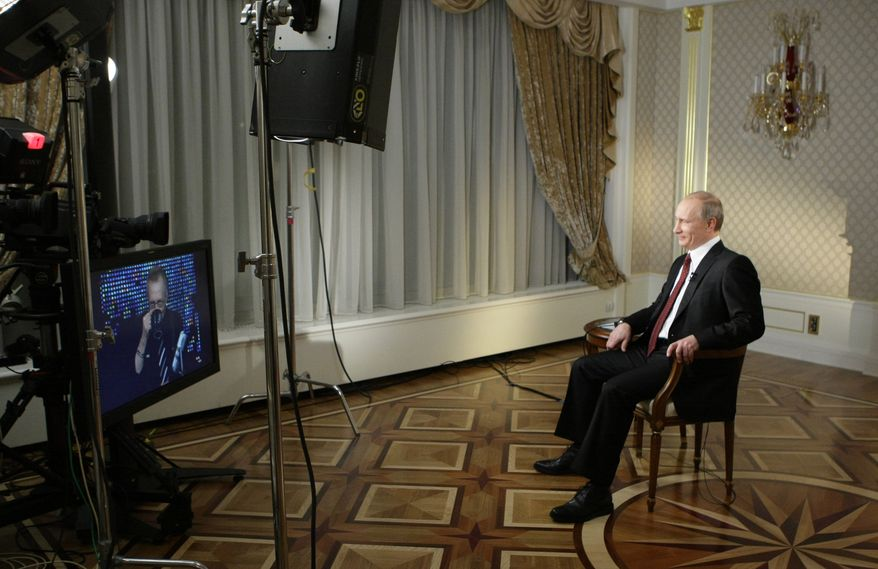 """Then-Russian prime minister, now president, Vladimir Putin records a CNN interview with Larry King in Moscow in 2010. King will host a new talk show, """"Politics With Larry King"""" for Russian TV network RT. (AP Photo/RIA Novosti, Alexei Nikolsky, Pool)"""