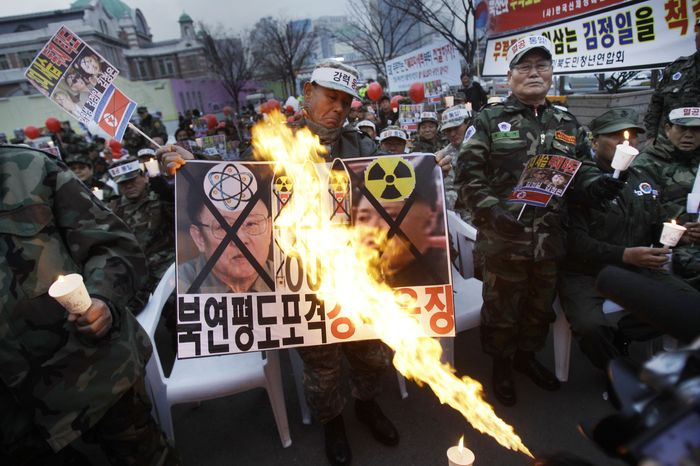 South Korean military veterans burn banners against North Korean leader Kim Jong-il and his son Kim Jong-un during a protest in Seoul on Thursday, Dec. 2, 2010. (AP Phot