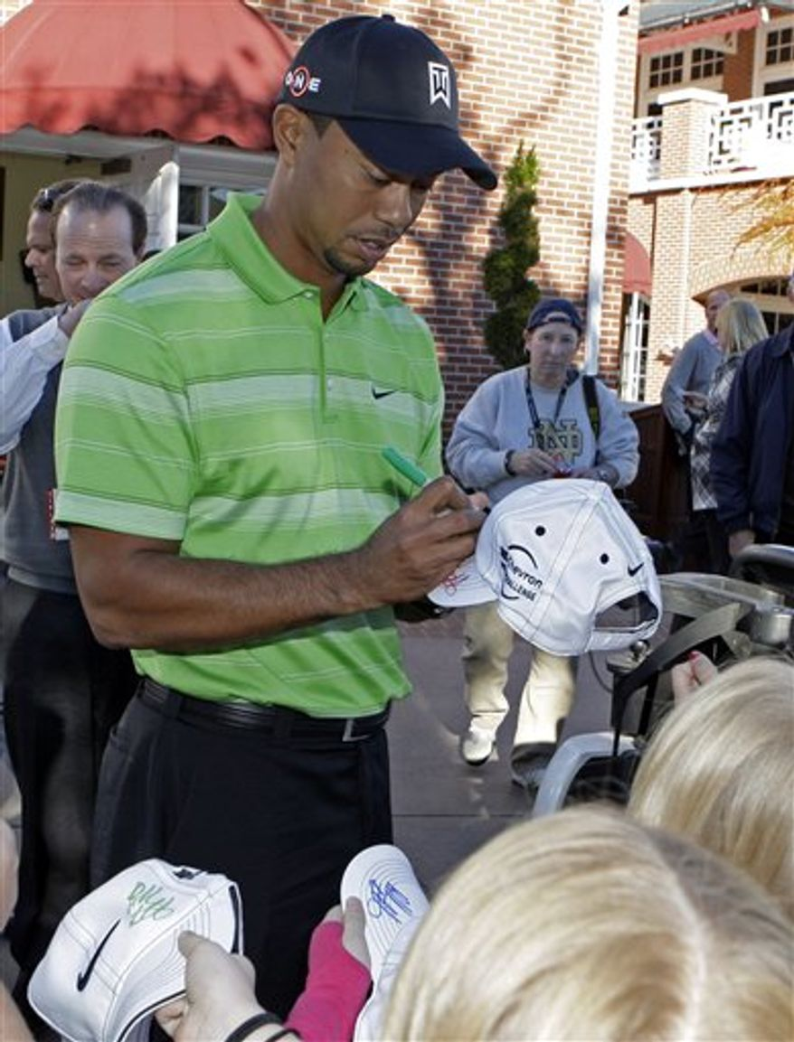 Tiger Woods signs autographs at the the Chevron World Challenge golf tournament at Sherwood Country Club in Thousand Oaks, Calif., Tuesday, Nov. 30, 2010.  (AP Photo/Reed Saxon)