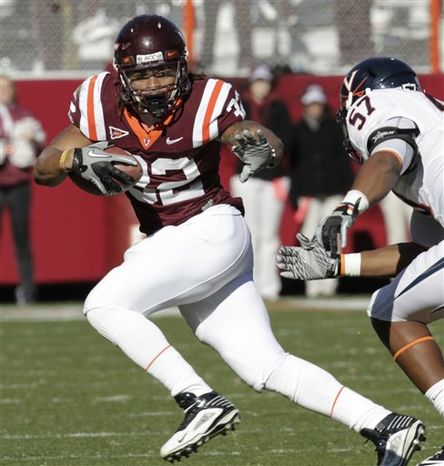 FILE - In this Nov. 27, 2010, file photo Virginia Tech running back David Wilson (4), left,  stretches in for a touchdown as Virginia cornerback Chase Minnifield (13) tries to make the stop during the first half  of an NCAA college football game at Lane Stadium in Blacksburg, Va.  The No. 12 Hokies are on the brink of another ACC championship and a berth in the Orange Bowl. (AP Photo/Steve Helber, File)
