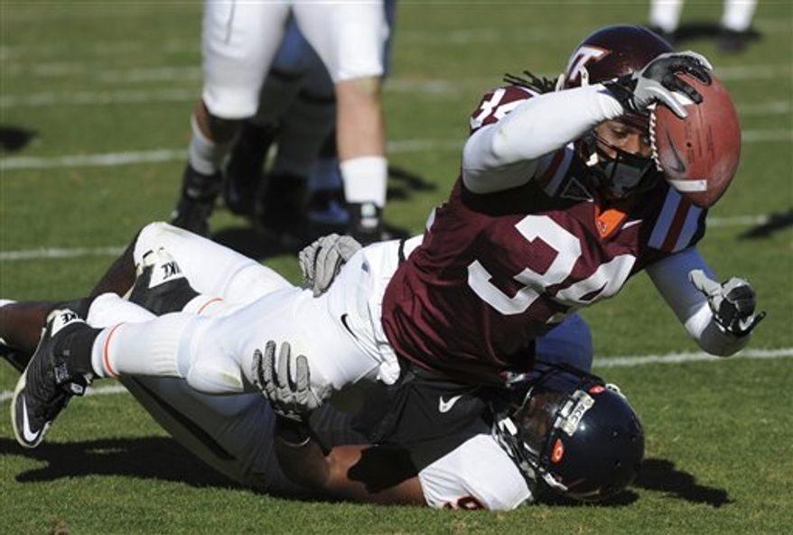 FILE - In this Nov. 27, 2010, file photo Virginia Tech  running back Ryan Williams (34) stretches for a touchdown as Virginia linebacker LaRoy Reynolds tries to make the stop during the second half of an NCAA college football game at Lane Stadium in Blacksburg, Va.  Williams is the touchdown maker, as likely to run away from a defender as run over him.  (AP Photo Don Petersen, File)
