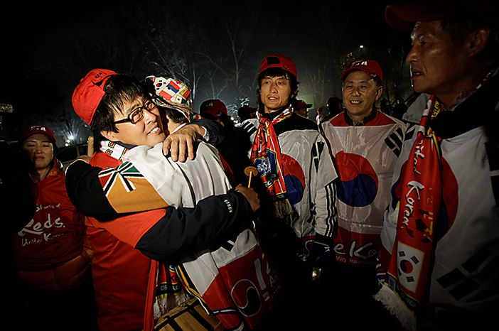 South Korean football fans console each other after losing the bid for the 2022 World Cup, Friday, Dec. 3, 2010 in Gwacheon, South Korea. In the end Russia won the bid for 2018 and Qatar took 2022.  (AP Photo/Wally Santana)