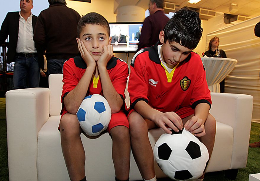 Two young bosys react after watching a live viewing of the 2018 and 2022 World Cup hosts, at the King Baudouin stadium in Brussels, Thursday Dec. 2, 2010. Soccer's world governing body FIFA chose Thursday, the hosts for the 2018 and 2022 World Cups in Zurich, Switzerland. The 2018 World Cup will be organized in Russia. (AP Photo/Yves Logghe)