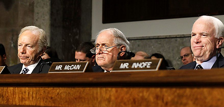 Senate Armed Services Committee Chairman Sen. Carl Levin, D-Mich., center, flanked by the the committee's ranking Republican Sen. John McCain, R-Ariz., right, and Sen. Joseph Lieberman, I-Conn., listens to testimony  on Capitol Hill in Washington Thursday, Dec. 2, 2010, during the committee's hearing on the military Don't Ask Don't Tell policy. (AP Photo/Alex Brandon)