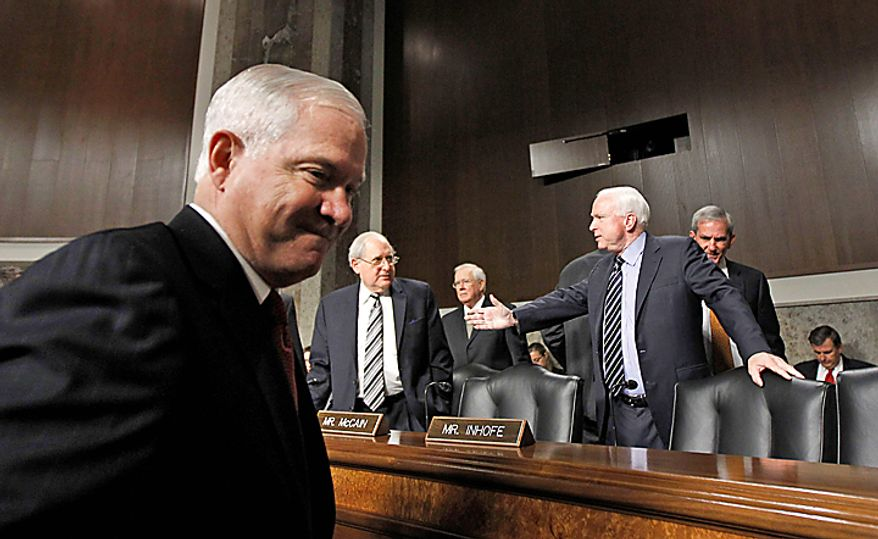 Defense Secretary Robert Gates, left, arrives on Capitol Hill in Washington Thursday, Dec. 2, 2010, to testify before the Senate Armed Services Committee hearing about the Don't Ask Don't Tell policy. Committee Chairman Sen. Carl Levin, D-Mich., is at center, the committee's ranking Republican Sen. John McCain, R-Ariz. is at right. (AP Photo/Alex Brandon)