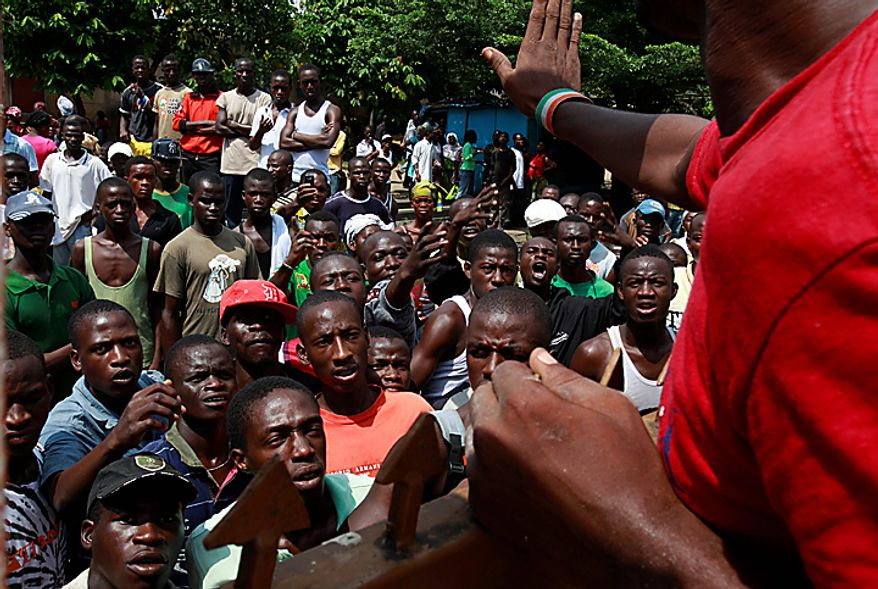 A man tries to calm opposition party supporters as they shout to be let into the local party office following a deadly overnight attack in the Yopougon neighborhood of Abidjan, Ivory Coast, on Thursday, Dec. 2, 2010. Gunmen attacked an office of presidential candidate Alassane Ouattara, killing at least four people, authorities said, as Ivory Coast tensely awaited election results, the release of which was blocked by the president's followers. The unidentified assailants used automatic weapons during the overnight attack and were able to get to the site and escape despite a curfew. (AP Photo/Rebecca Blackwell)