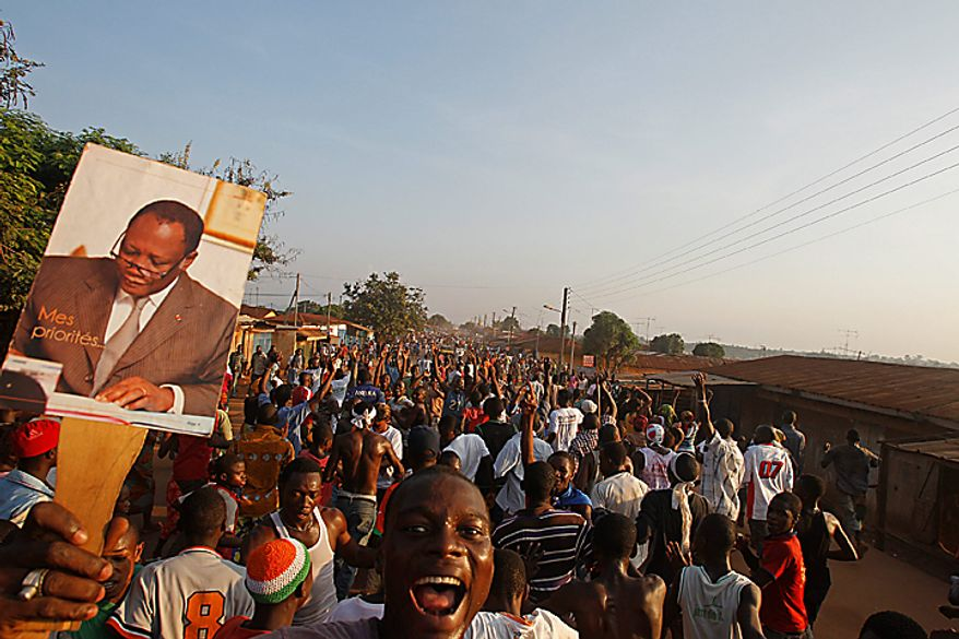 People in Gagnoa, Ivory Coast, react on Thursday, Dec. 2, 2010, to the news that Ivory Coast opposition leader Alassane Ouattara, shown in the hand-held poster, was named winner of the country's first presidential election in a decade. (AP Photo/Schalk van Zuydam)