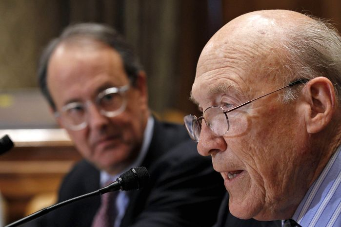** FILE ** In this Nov. 10, 2010, file photo, Erskine Bowles, left, watches former Wyoming Sen. Alan Simpson, co-chairman of President Barack Obama's bipartisan deficit commission, speak at a news conference on Capitol Hill in Washington. (AP Photo/Alex Brandon, File)