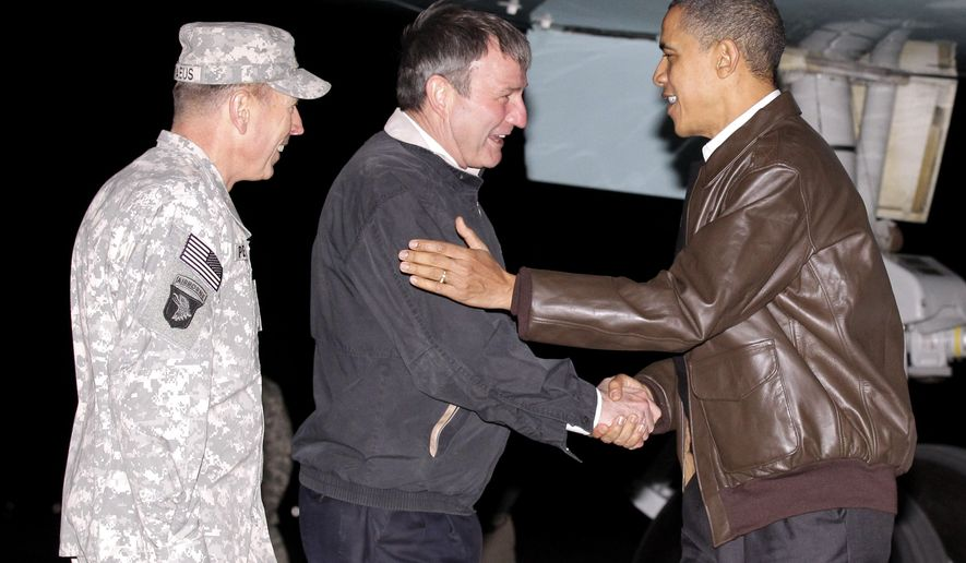 President Barack Obama is greeted by NATO Commander in Afghanistan Gen. David Petraeus, left, and U.S. Ambassador to Afghanistan Karl W. Eikenberry, center, after stepping off Air Force One during an unannounced visit to Bagram Air Base in Afghanistan on Friday, Dec. 3, 2010. (AP Photo/Pablo Martinez Monsivais)