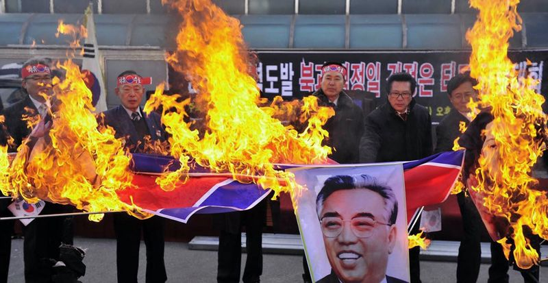 South Korean military veterans burn a North Korean flag and portrait of Kim Il Sung, the late founder of North Korean, during a rally denouncing last week's North Korean bombardment on a South Korean border island, in Jecheon, South Korea, on Friday, Dec. 3, 2010. President Lee Myung-bak&am