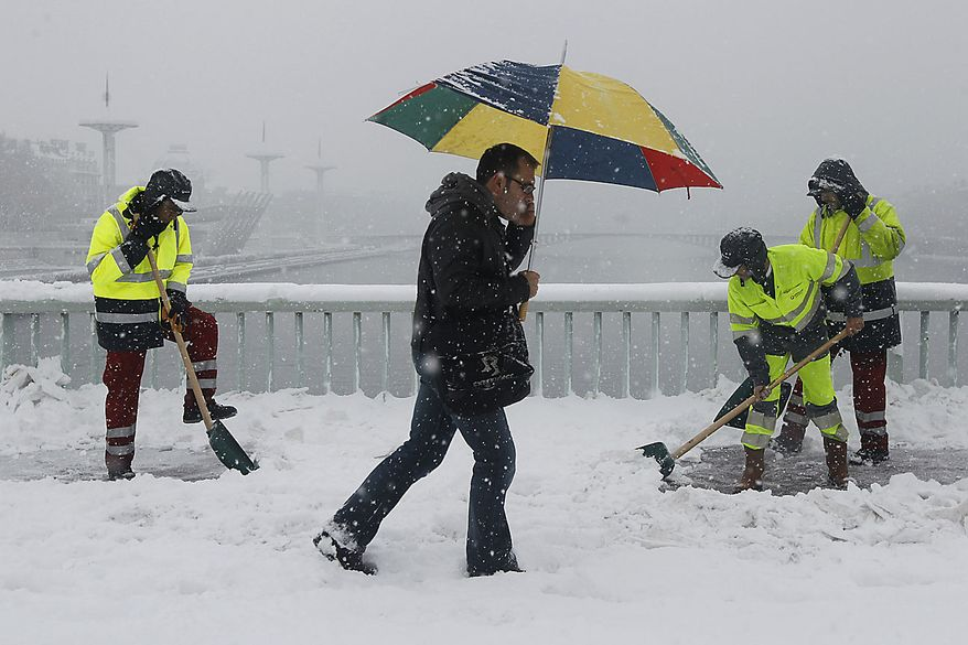 A man walks as workers shovel the snow on the walkway, in Lyon, central France, Wednesday, Dec. 1, 2010. Heavy snow and subzero temperatures swept across Europe, killing at least eight homeless people in Poland, closing major airports in Britain and Switzerland, and causing delays to rail and road traffic across the continent. (AP Photo/Laurent Cipriani)