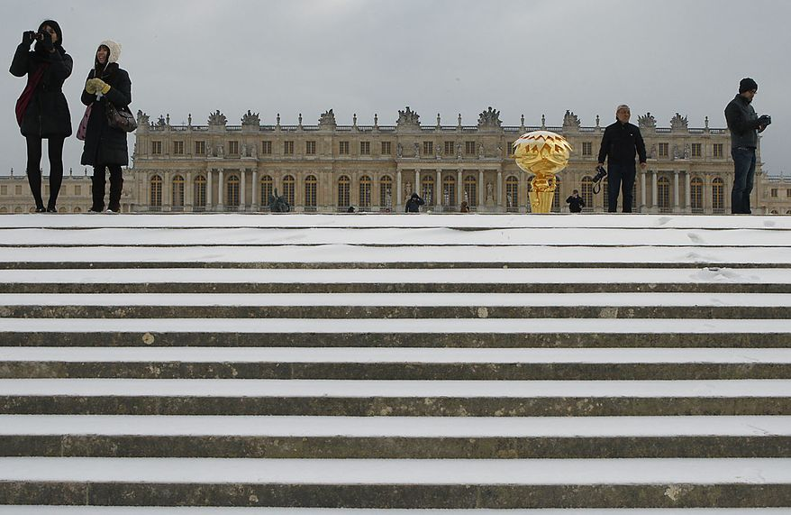 Snow covers the steps leading to the Chateau de Versaille, as Japanese tourists take pictures in Versailles, west of Paris, Thursday, Dec. 2, 2010. Heavy snow and subzero temperatures swept across Europe, killing at least eight homeless people in Poland, closing major airports in Britain and Switzerland, and causing delays to rail and road traffic across the continent.(AP Photo/Michel Euler)