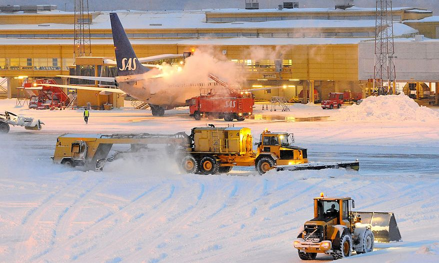 An SAS 737 aircraft is deiced as snowplows struggle to clear the runway at Malmo airport, Southern Sweden on Dec. 2, 2010. The airport was shut down Thursday as heavy snowfall and freezing temperatures hit Northern Europe for the third straight day. (AP Photo /Johan Nilsson)