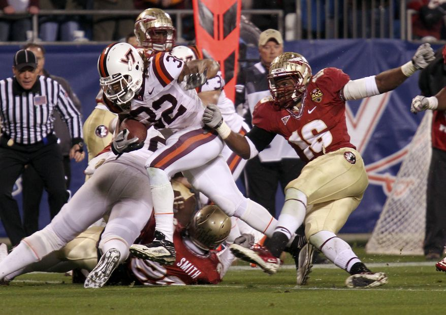 Virginia Tech's Darren Evans (32) runs past Florida State's Mister Alexander (16) for a touchdown in the first half of the Atlantic Coast Conference championship game in Charlotte, N.C., on Dec. 4, 2010. (Associated Press)