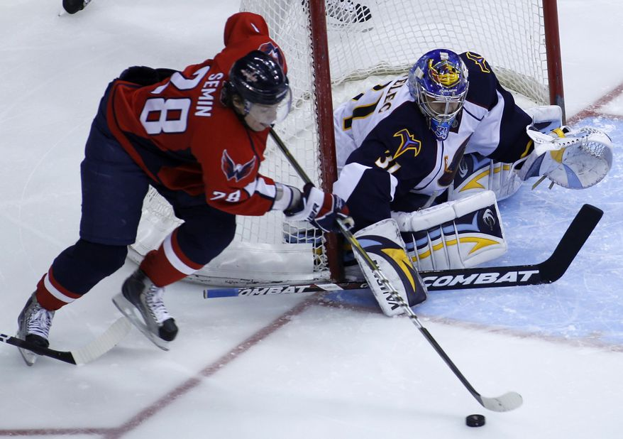 Washington Capitals' Alexander Semin (28), of Russia, moves the puck as Atlanta Thrashers goalie Ondrej Pavelec, right, of the Czech Republic, defends during the third period of an NHL hockey game Saturday, Dec. 4, 2010, in Washington. The Thrashers won 3-1. (AP Photo/Luis M. Alvarez)