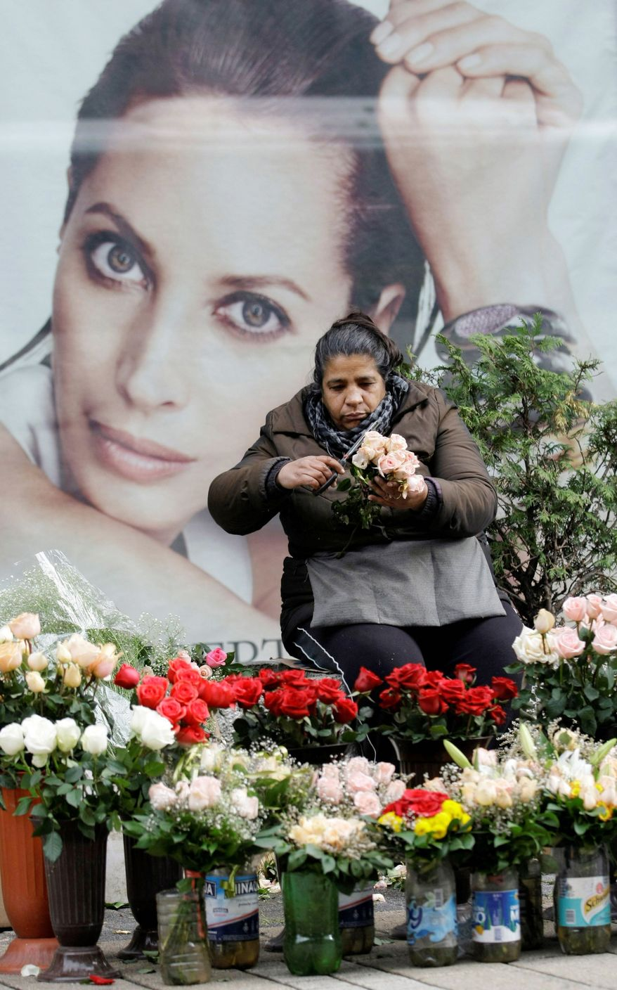A Roma woman arranges flowers for sale against the background of an advertisement featuring American model Christy Turlington in the street in downtown Belgrade, the Serbian capital. Serbia has made some important steps on its way toward joining the European Union and breaking up with the wartime past. (Associated Press)