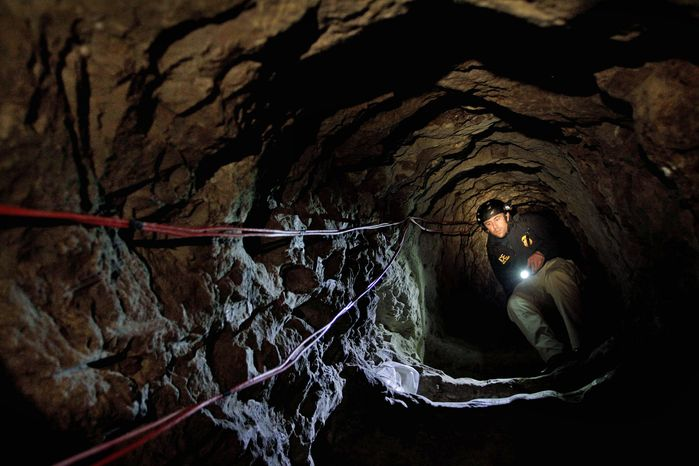 ** FILE ** A U.S. Immigration and Customs Enforcement agent inspects a tunnel that authorities discovered Nov. 25, 2010, and say was used to smuggle drugs from Mexico to an Otay Mesa warehouse in San Diego. (Associated Press)