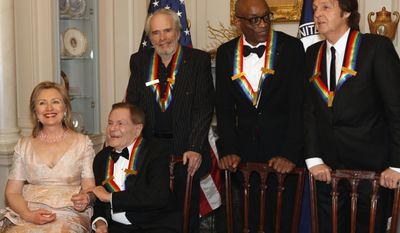 Secretary of State Hillary Rodham Clinton talks with Kennedy Center honorees (from second from left) Jerry Herman, Merle Haggard, Bill T. Jones and Paul McCartney while waiting for Oprah Whitney to arrive for a group photo after a dinner at the State Department in Washington on Saturday, Dec. 4, 2010. (AP Photo/Jacquelyn Martin)