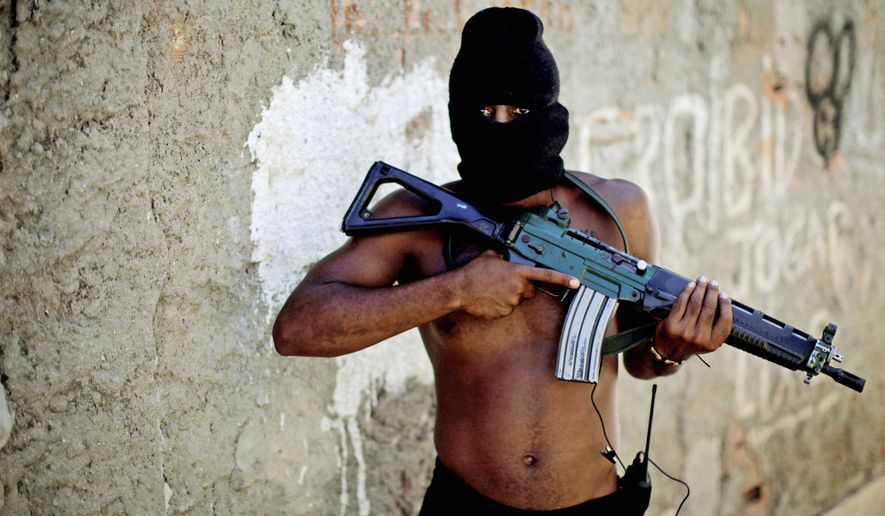 "A self-identified drug trafficker poses in a Rio slum. ""You take any animal and put it up against the wall,"" he says, describing gang response to the slum crackdown. ""Its last option is what? To attack."" (Associated Press)"