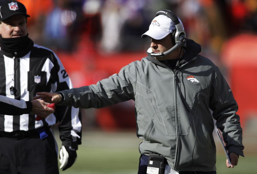 Denver Broncos coach Josh McDaniels, right, takes back his replay flag from a game official during the first half of an NFL football game against the Kansas City Chiefs at Arrowhead Stadium in Kansas City, Mo., Sunday, Dec. 5, 2010. (AP Photo/Orlin Wagner)