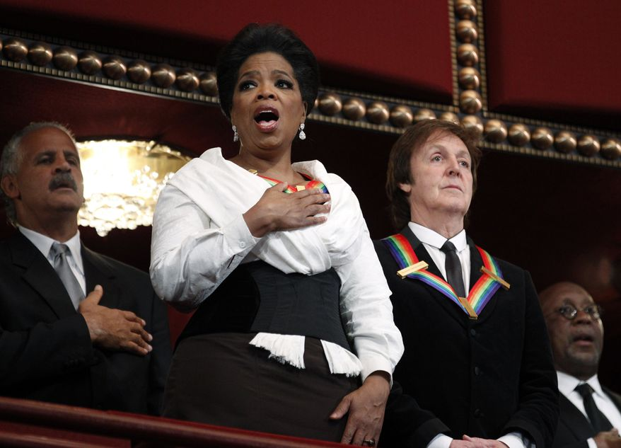 Recipients of the 2010 Kennedy Center Honors, Oprah Winfrey, and Paul McCartney, sing the National Anthem during the 2010 Kennedy Center Honors Gala at the Kennedy Center in Washington, Sunday, Dec. 5, 2010. Others are Stedman Graham, back left, and Trade Representative Ron Kirk, back right. (AP Photo/Manuel Balce Ceneta)