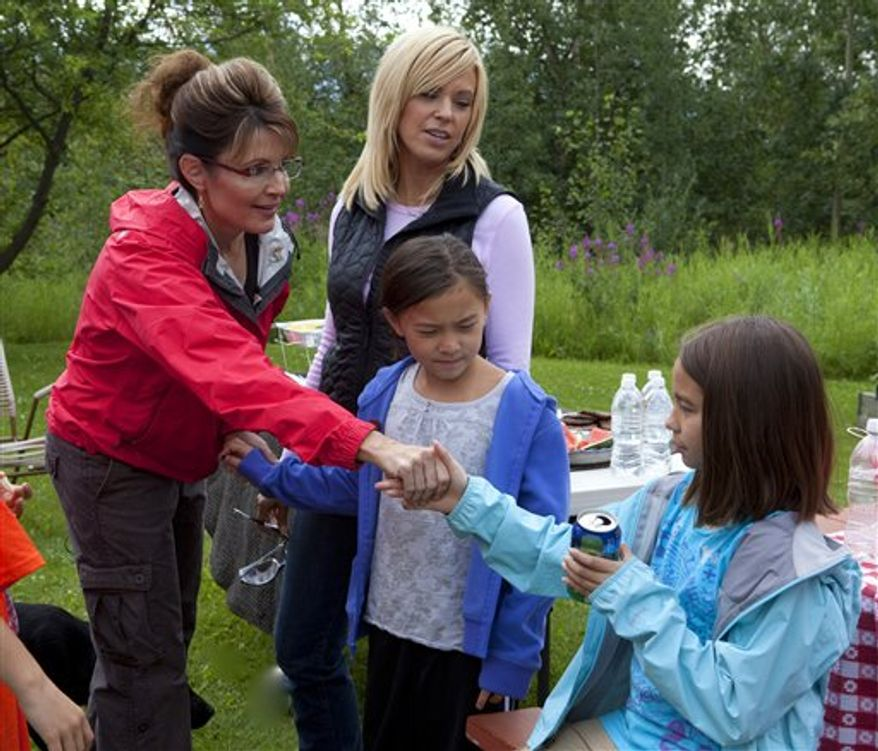 "In this July 2010 photo released by TLC, former Alaska Gov. Sarah Palin helps sextuplet Leah Gosselin as she cooks a hotdog on an open flame, in Coffee Creek, Alaska, during a taping of ""Sarah Palin's Alaska.""  The Gosselin-Palin camping trip will air on Sunday, Dec. 12, at 9 p.m. EST on TLC. (AP Photo/TLC, Gilles Mingasson)"