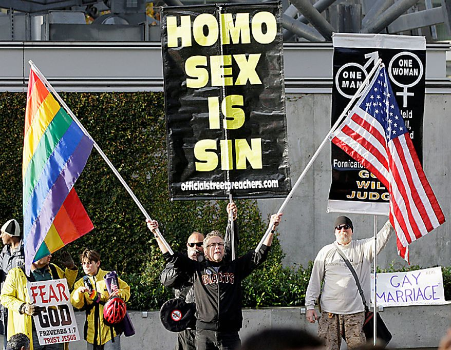 In this Dec. 6, 2010 file photo, Billy Bradford, foreground, holds up a rainbow flag and an American flag in front of opponents of gay marriage across the street from the courthouse before a hearing in the Ninth Circuit Court of Appeals in San Francisco. (AP Photo/Jeff Chiu, file) ** FILE **