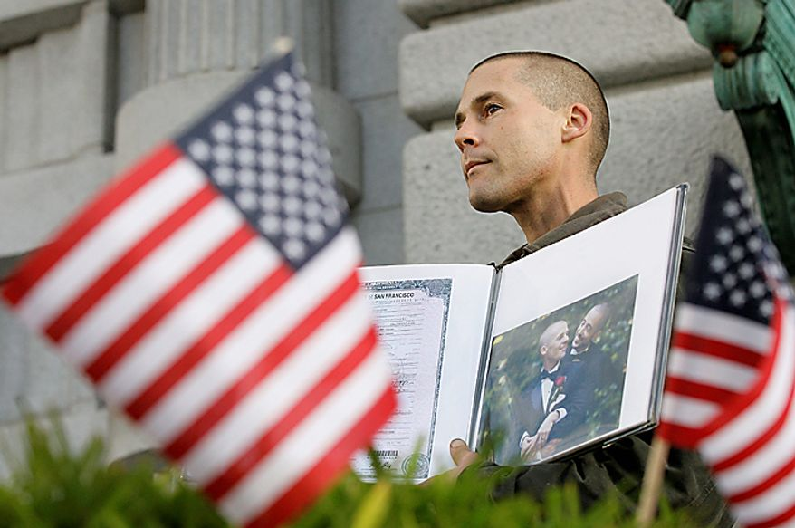 Frank Capley-Alfano holds up a book with a photo of him and his husband Joseph outside the courthouse before a hearing in the Ninth Circuit Court of Appeals, Monday, Dec. 6, 2010, in San Francisco. The federal appeals court in San Francisco began to hear arguments Monday about the voter-approved ban known as Proposition 8. A trial court judge overturned the measure as a violation of gay Californians' civil rights in August. (AP Photo/Jeff Chiu)