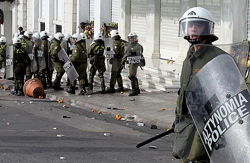 A riot policeman reacts during clashes with youths in Athens on Monday, Dec. 6, 2010. Youths hurled rocks and oranges at a government building in central Athens during a student protest to mark two years since the fatal police shooting of a teenage boy that sparked Greece's worst riots in decades. Police closed roads and deployed several thousand officers around the city but maintained a minimal presence at the site where some 1,500 students gathered outside Athens University's main buildings. (AP Photo/Thanassis Stavrakis)